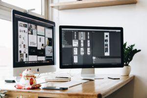 Ordinateur connecté à deux écrans posés sur un bureau