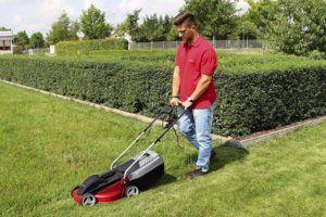 Un homme coupant sa pelouse avec un tondeuse à gazon électrique
