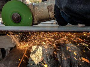 Un homme découpe dans le métal avec une meuleuse d'angle.
