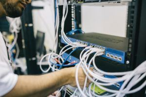 Un homme essayant de connecter le réseau de distribution de connexion internet.