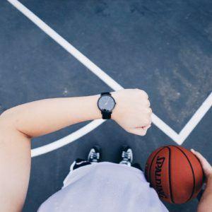 Un homme qui tient un ballon de basket en main en regardant l'heure sur sa montre.