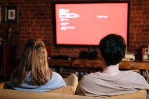 Un couple assis dans un canapé en train de regarder la télévision