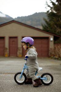 Une fillette qui fait du vélo avec son casque de protection sur la tête