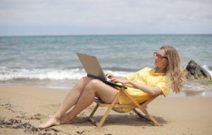 Une jeune femme assise sur une chaise pliante sur la plage