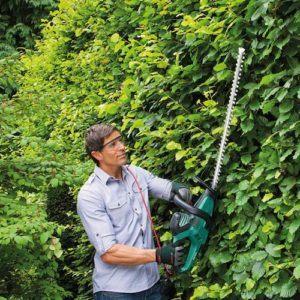 Un homme qui utilise un appareil puissant pour effectuer des coupes d'herbes.