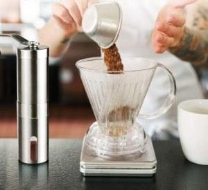 Une personne remplissant un verre avec du café fraîchement moulu.