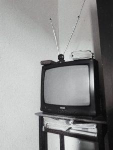 Une télévision analogique avec une antenne intérieure posée au-dessus.