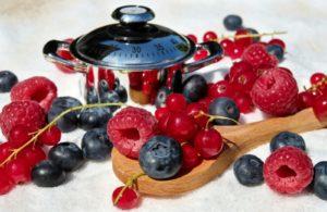 Une marmite de cuisson avec des fruits de fraises autour.