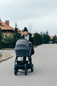 Une femme qui conduit son enfant dans une poussette.