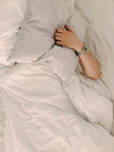 Une personne se couvrant le visage avec un oreiller.