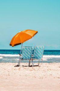 Des chaises installées au bord de mer avec un parasol.