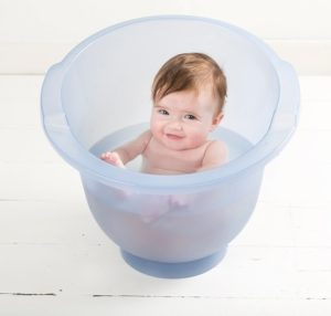 Dans un seau de bain, votre enfant s'assoit à la verticale dans celui qui se trouve dans le seau.
