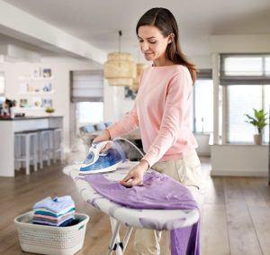 Une femme qui utilise un fer à repasser sur des vêtements.