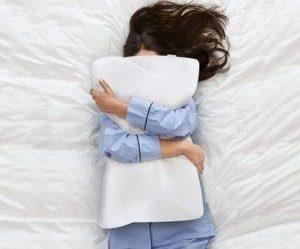 Une femme embrasse un oreiller dans son lit.