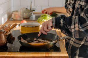 Une femme qui fait la cuisine sur une plaque à induction