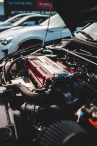 Un véhicule avec le capot ouvert laisse entrevoir une batterie de voiture