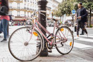 Un vélo attaché à un poteau sur une voie publique