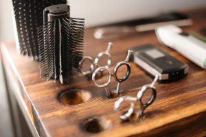 Deux brosses à cheveux sur une table avec des ciseaux.