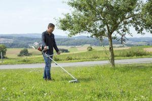 Un homme coupant l'herbe avec un coupe-bordure thermique IKRA IBF 25-1.
