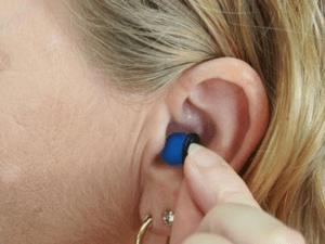 Femme mettant un appareil auditif bleu