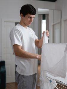 Homme en t-shirt blanc manipulant du linge blanc à côté d'un étendoir à linge