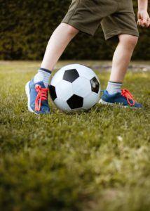 Les pieds d'un enfant qui joue avec un ballon de foot