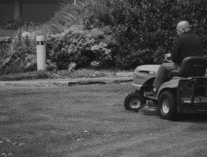 Photo noir et blanc d'un homme conduisant un tracteur tondeuse