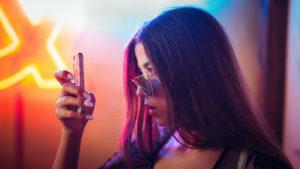Une femme qui regarde sur l'écran de son téléphone portable.