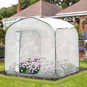 Cette serre de jardin a un design moderne et attirant.